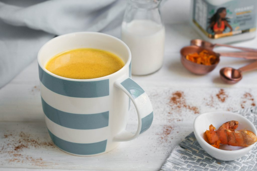 Turmeric Golden Milk in blue and white striped mug with fresh turmeric