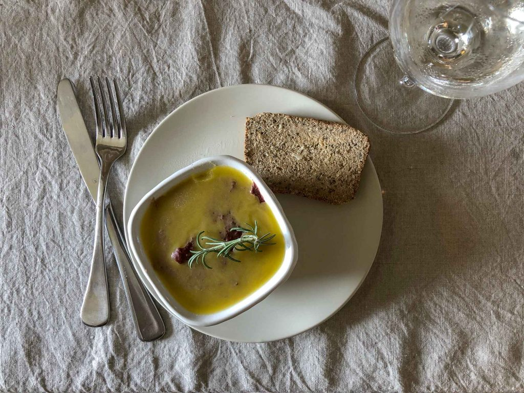 Chicken Liver pate in a pot on a linen tablecloth with bread