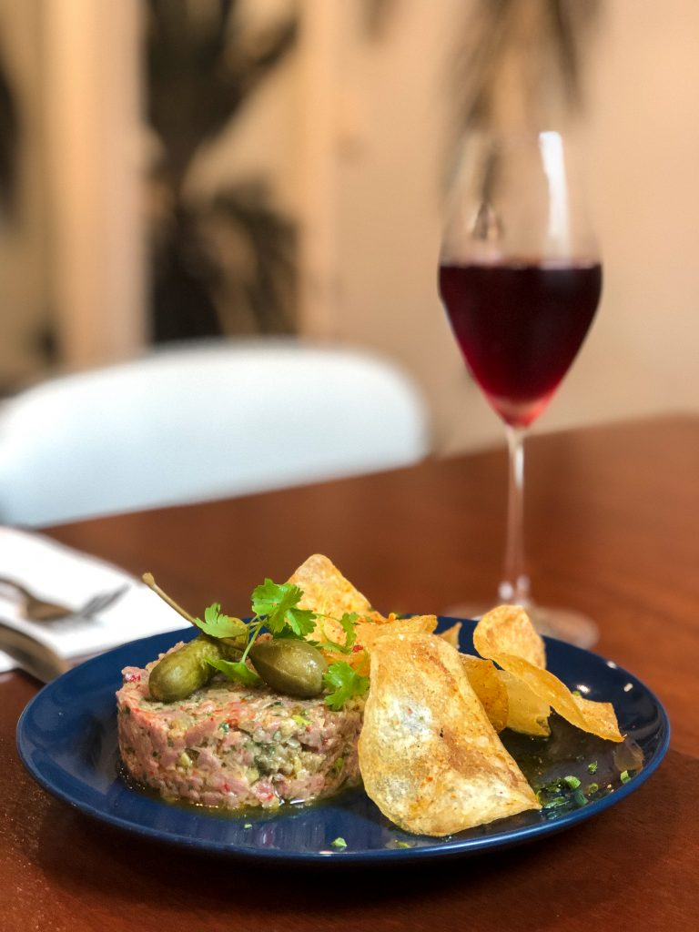 Dining table with beef tartare on a plate and red wine glass
