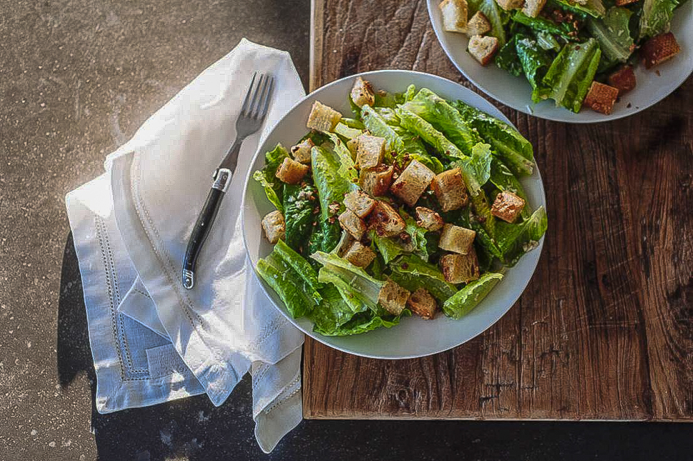 Bowl of fresh Caesar salad with napkin and fork